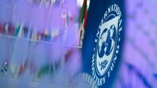 IMF logo against a backdrop of flags