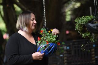A volunteer tends to a hanging basket made from an upcycled cycle helmet