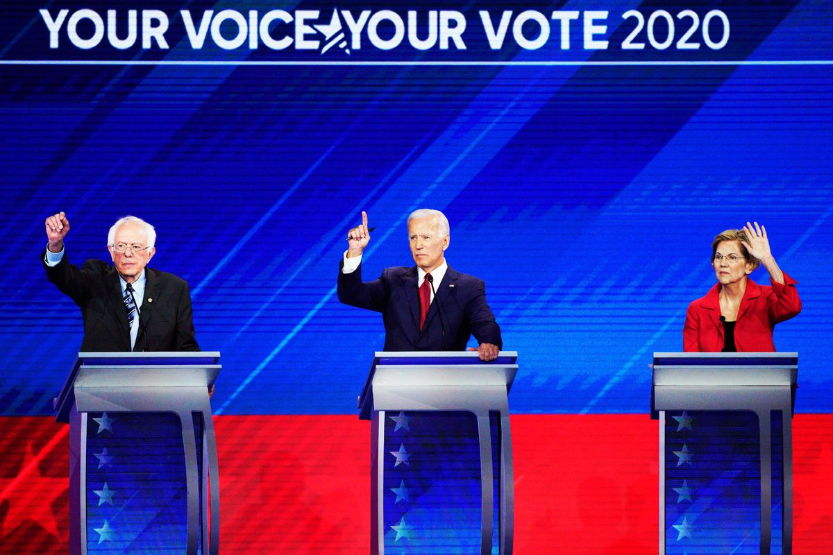Democratic presidential candidates Sanders, Biden, and Warren stand behind podiums and raise their hands to answer a question during a Democratic presidential primary debate.