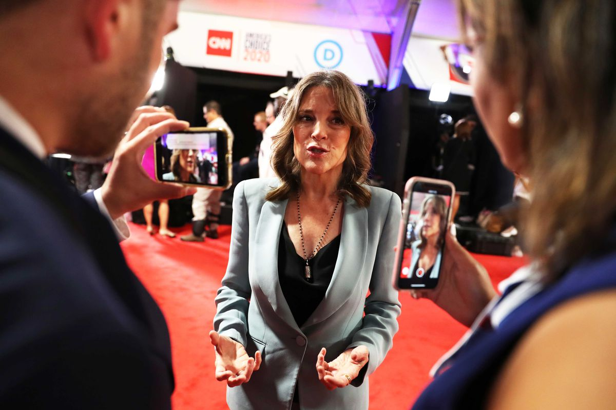 Two people take photos of Marianne Williamson with their phones in Detroit.